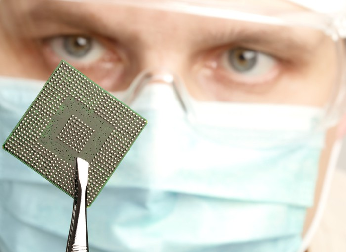 A technician, wearing goggles and a face mask, holds up a semiconductor chip for a close inspection.