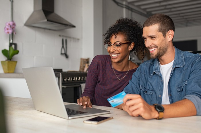 Two people with credit card, using laptop