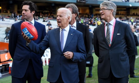 Joe Biden holds up an AFL football at the Melbourne Cricket Ground, 17 July 2016